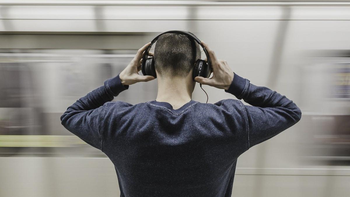 アイキャッチ:通過する列車とヘッドホンをする男性